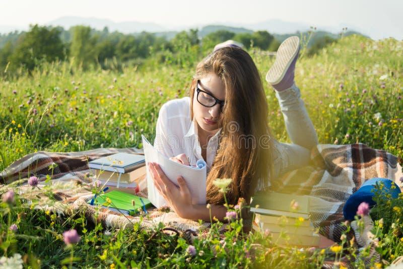Gril che si trova sull'erba e che scrive sul taccuino fotografia stock libera da diritti