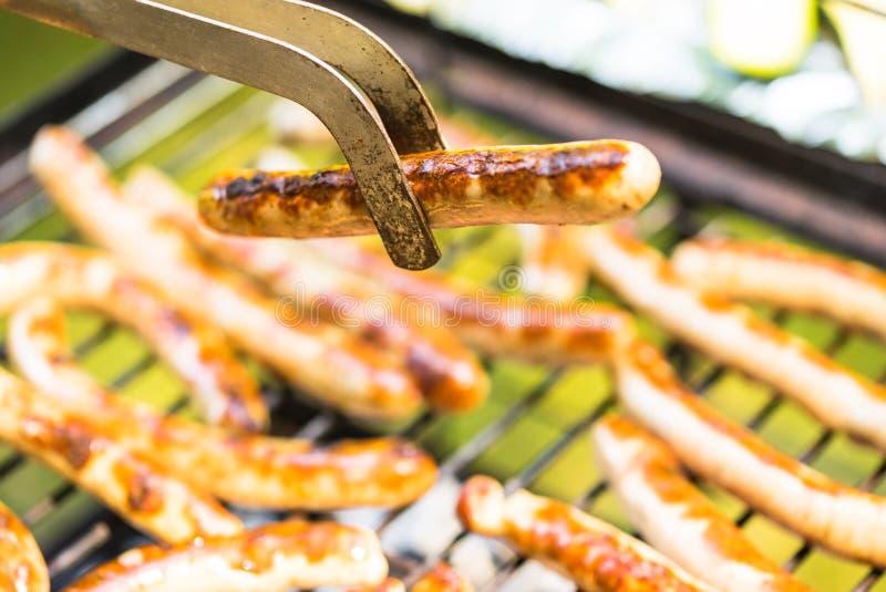 Gril de barbecue avec les saucisses grillées et la saucisse frite se tenant avec des pinces de barbecue photo stock