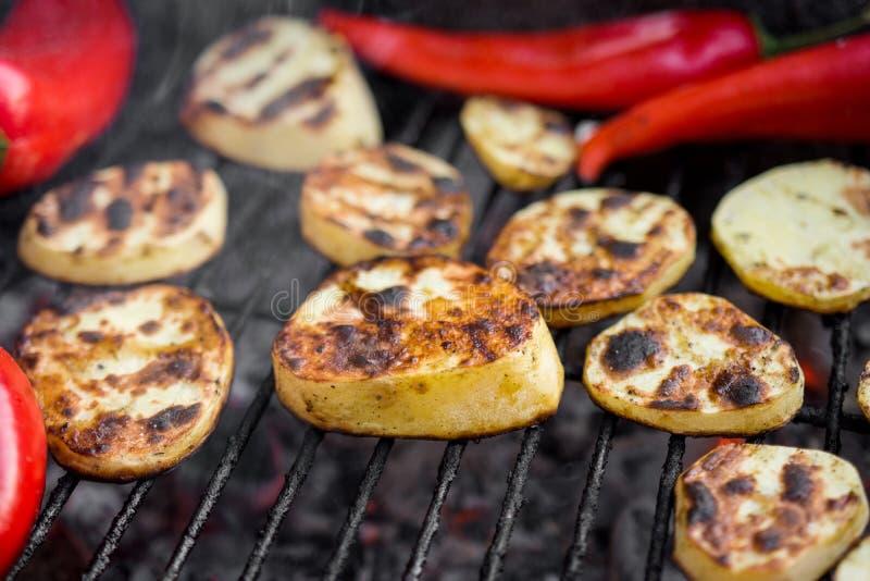 Gril de BBQ avec des morceaux de pommes de terre d'une coupe, des poivrons rouges et le blanc de poulet savoureux images libres de droits