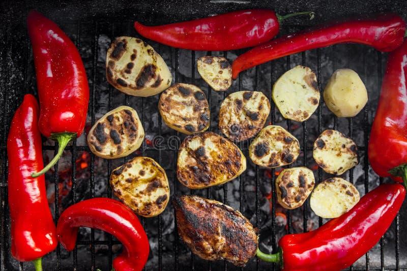 Gril de BBQ avec des morceaux de pommes de terre d'une coupe, des poivrons rouges et le blanc de poulet savoureux photographie stock