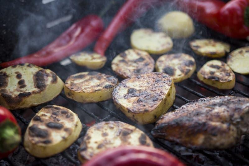 Gril de BBQ avec des morceaux de pommes de terre d'une coupe, des poivrons rouges et le blanc de poulet savoureux photos stock