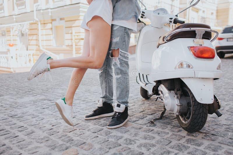 Gril hoppar nära grabb Hon ben är i luft De står bredvid motorcykeln i mitt av gatan De har a royaltyfri foto