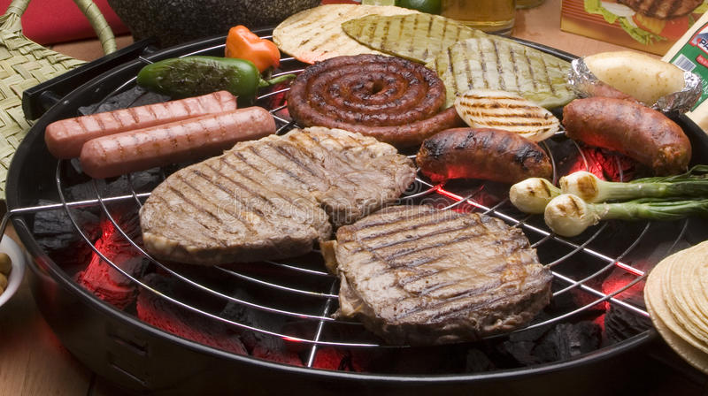 Grill. Beef, hot dog and sausage, with ingredients on the grill stock photography