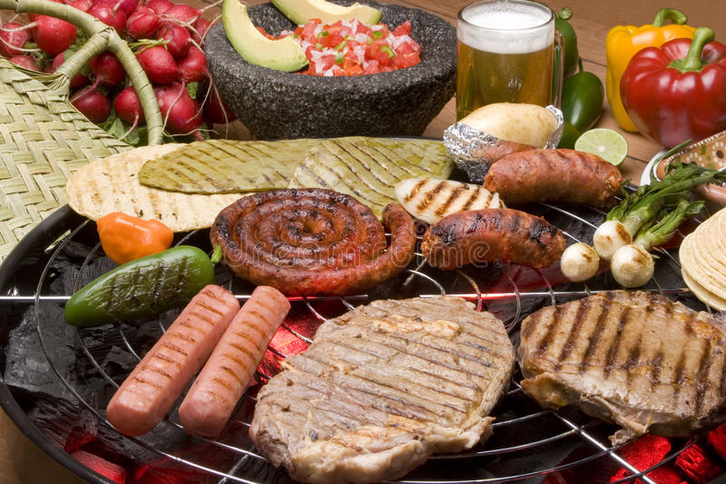 Grill. Steak, hotdog and sausage, with ingredients on the grill stock photography