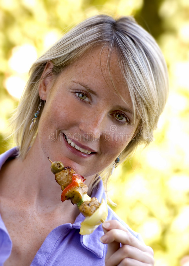 Grill. Young woman eating chicken on a grill spit portrait stock photos