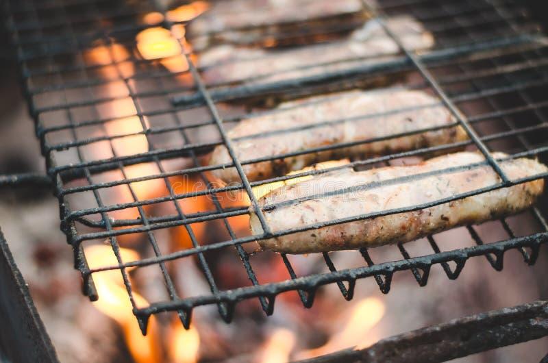 Grill auf nackter Flamme/Würsten eines Grills werden auf einem Messingarbeiter, Draufsicht gebraten lizenzfreie stockfotografie