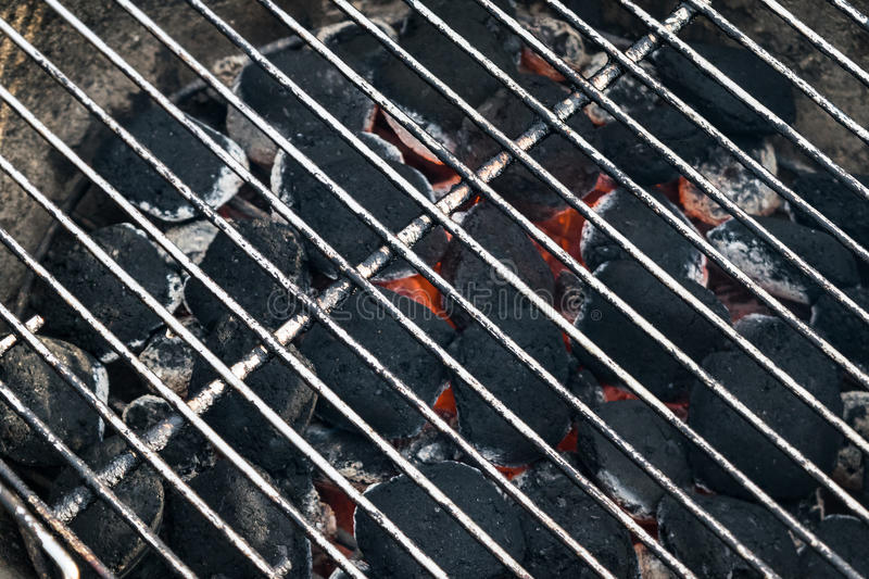 Grill charcoal bbq briquettes with hot metal grid royalty free stock photography