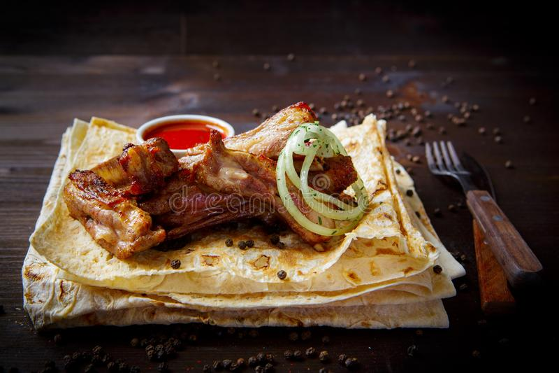 Grill dishes for the restaurant menu. Wooden background. Fried or grilled lamb ribs, onion and sauce stock image