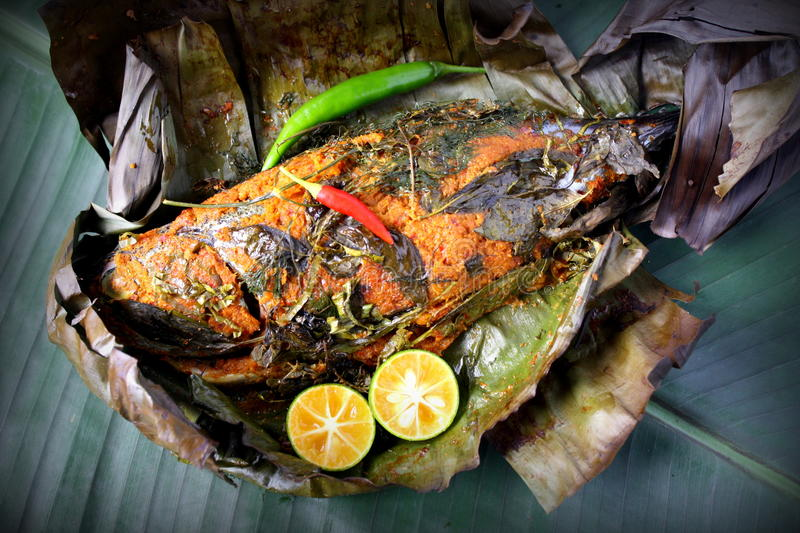 Grill Fish - Ikan Bakar. Ikan Bakar - Malaysian famous street food. Grill fish wrapped in banana leaf with a lots of spices royalty free stock photo