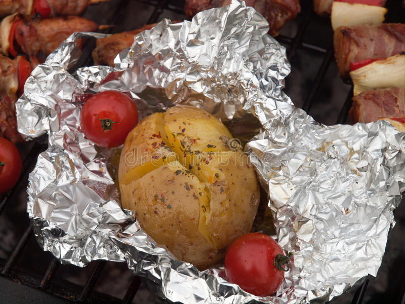 Grill food. Jacket potato from the braai wrapped in tinfoil with cherry tomato, red pepper flakes, garlic butter and parsley royalty free stock image