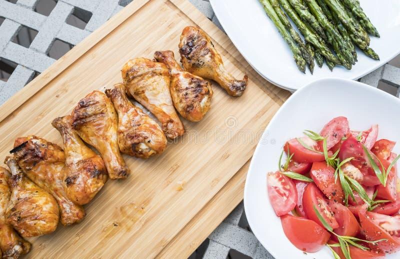 Grill-Hühnertrommelstöcke gedient mit gebratenem Spargel-und Tomaten-Salat stockfotografie
