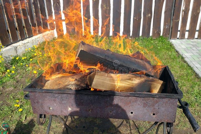 Grill mit brennendem Brennholz Vorbereitung der Kohle für Kebabs lizenzfreies stockbild