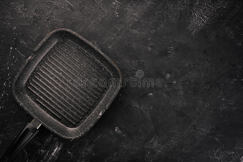 Grill pan for cooking. On a black stone background. Top view. Free copy space stock photo