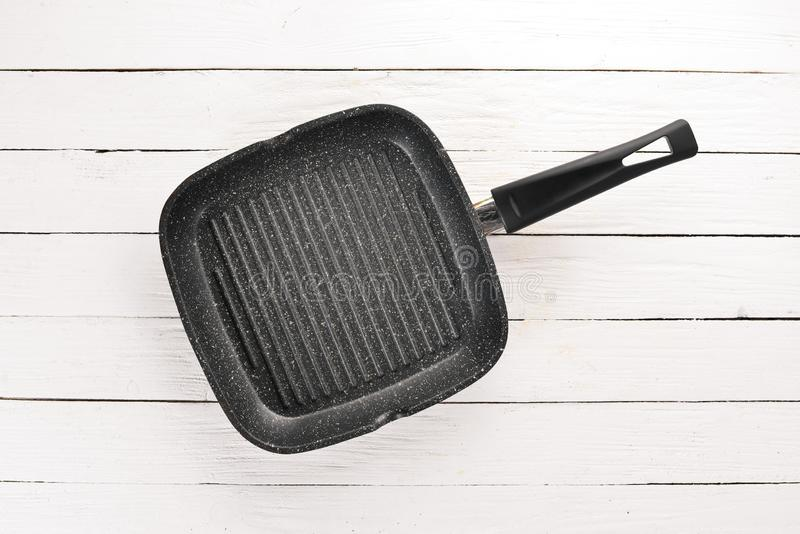 Grill pan for cooking. On a white wooden background. Top view. Free copy space stock photography