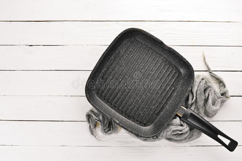 Grill pan for cooking. On a white wooden background. Top view. Free copy space royalty free stock photos