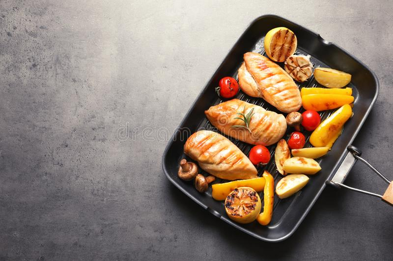 Grill pan with fried chicken breasts and garnish on grey background, top view. Space for text stock photography
