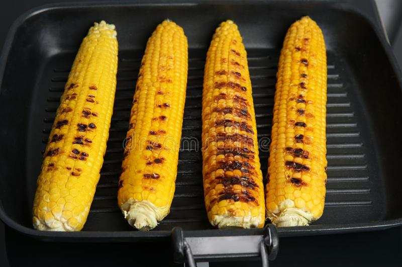 Grill pan with tasty fresh corn cobs on stove. Closeup stock photos
