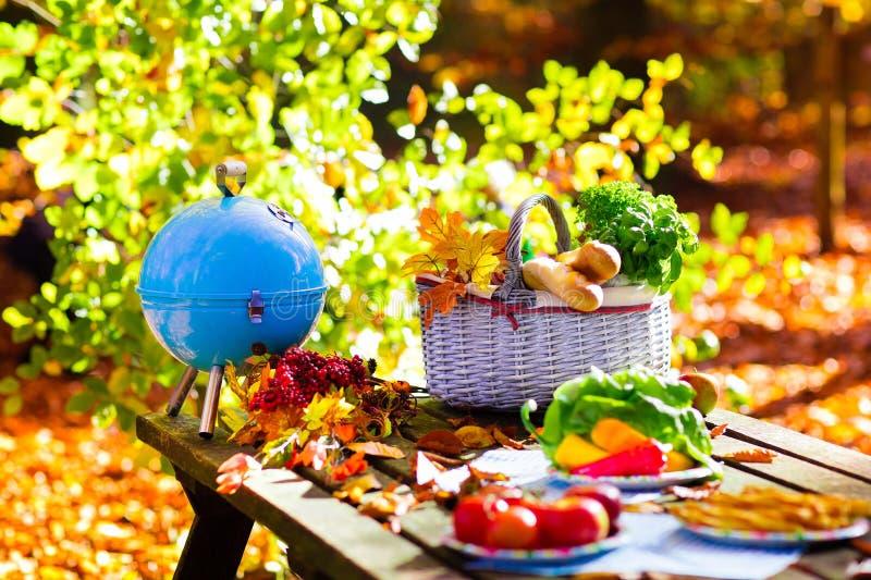 Grill and picnic basket in autumn garden stock photos