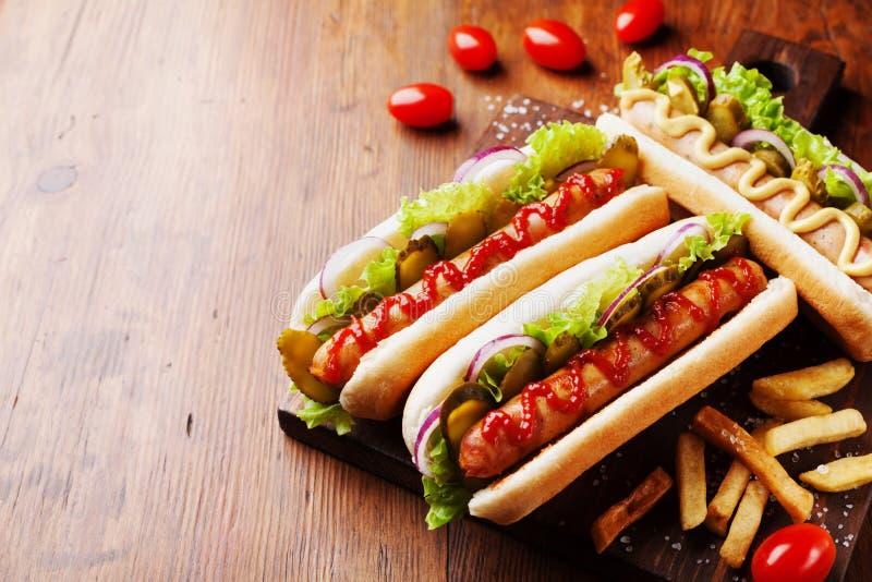 Grill piec na grillu hot dog z kiełbasianą i żółtą musztardą z ketchupem na drewnianej desce Tradycyjny Amerykański fast food obraz royalty free