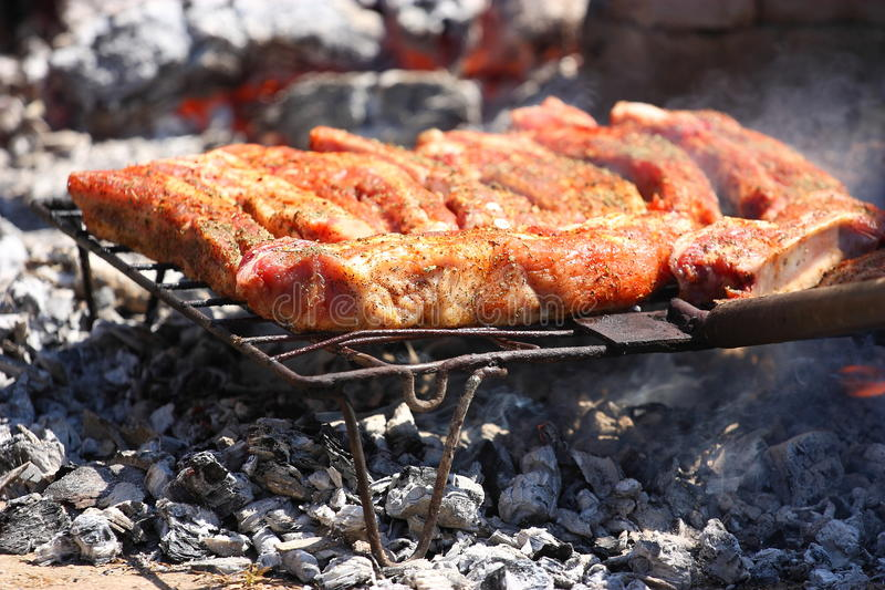 Grill. Pork ribs baking with charcoal on an outdoor grill stock photo