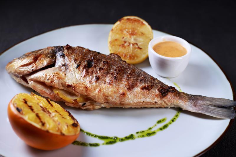 Grilled dorado fish with citrus and sauce. Grill pub and fish restaurant menu, proper nutrition, seafood, vegetarian, pescetarian. grilled dorado fish with royalty free stock photos