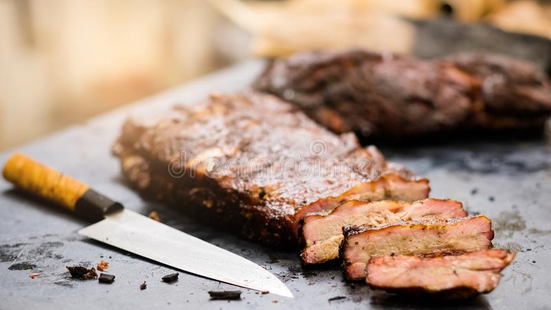 Grill restaurant smoked pork ribs kitchen table. Grill restaurant. Closeup of professional knife and sliced smoked pork ribs on kitchen table royalty free stock photography