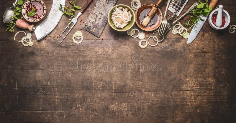 Grill seasoning and sauces with vintage kitchenware kitchen utensils Meat Fork and Butcher Cleaver , knife and herbs mezzaluna. Knife on wooden dark background royalty free stock images