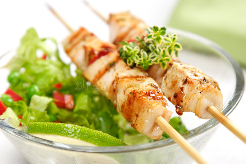 Grill spit. Pork (or chicken) on a grill spit with salad and a slice of lime and lemon-thyme as garnish stock image