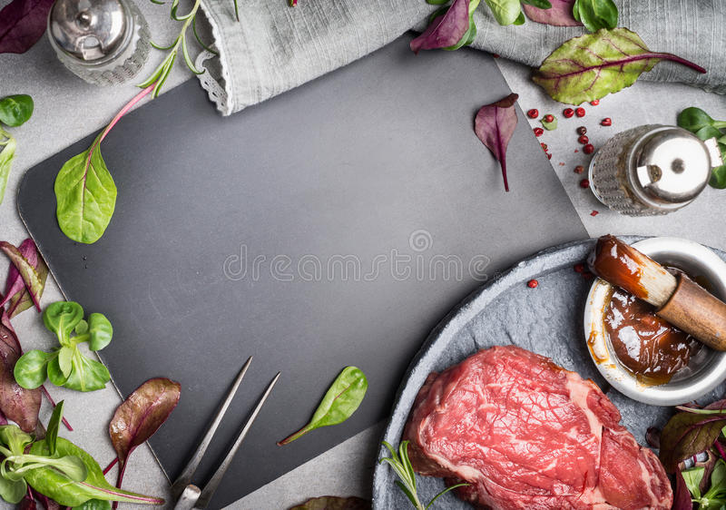Grill steak ingredients around blank chalkboard. Grill or BBQ steak marinating with Barbecue sauce stock images