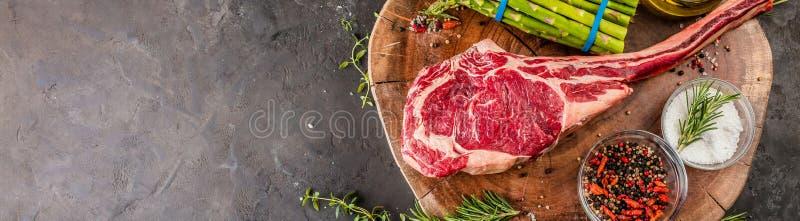 Grill trockenes gealtertes wagyu Kriegsbeilsteak mit grünem Spargel als Draufsicht über ein hölzernes Brett stockfotografie