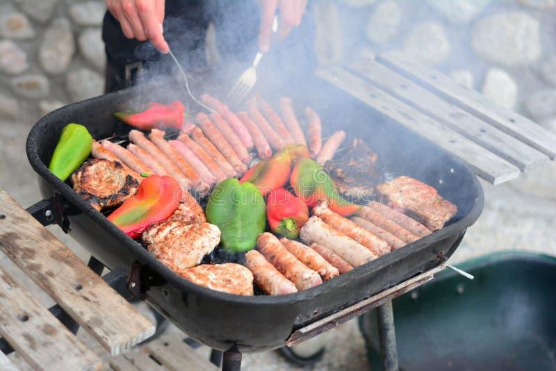 Grill z mięsem, kiełbasami i pieprzami gotuje na ogieniu, obrazy stock