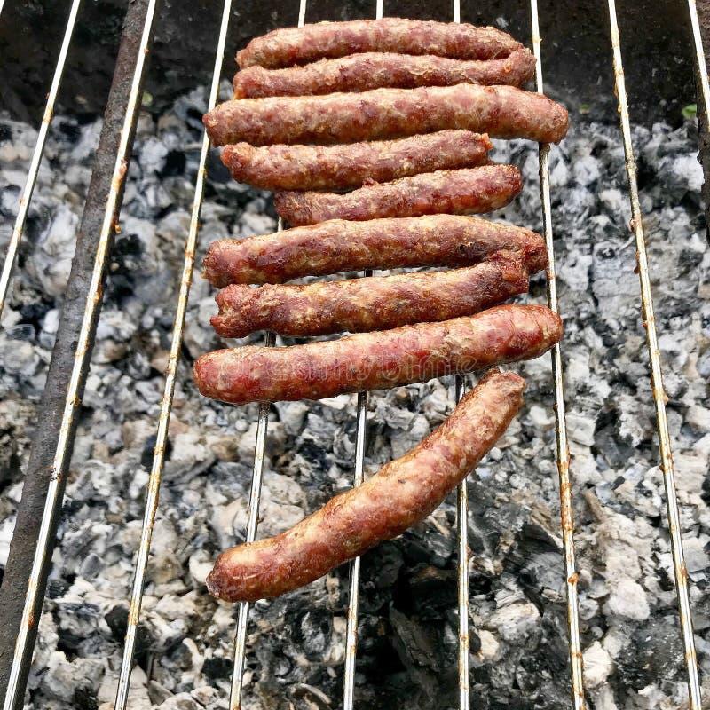 Grill z ognistymi Bawarskimi kiełbasami na grillu w ogródzie outdoors fotografia royalty free