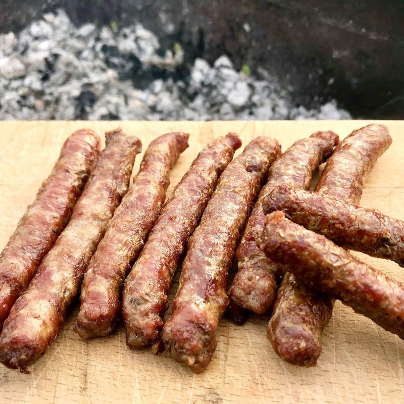Grill z ognistymi Bawarskimi kiełbasami na grillu w ogródzie outdoors zdjęcie stock