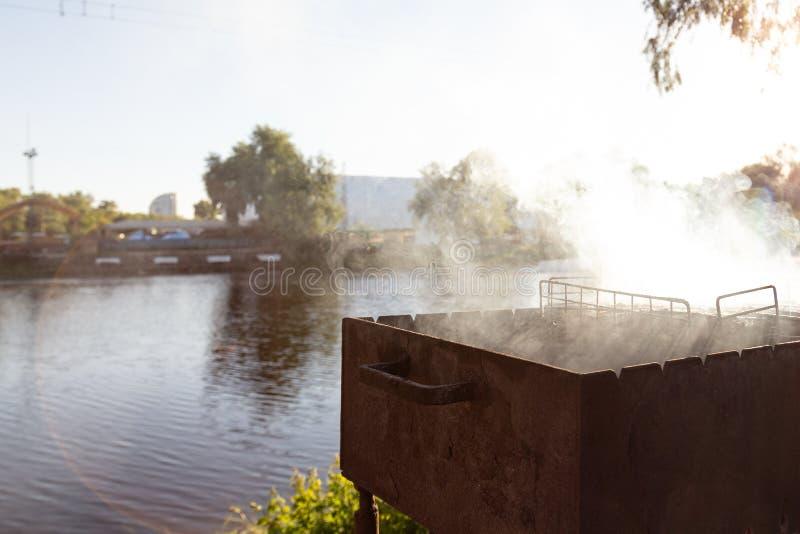 Grilla fyrpannan med tung rök under att grilla kött Utomhus- parti för BBQ nära sjön eller floden Copuspace arkivbilder