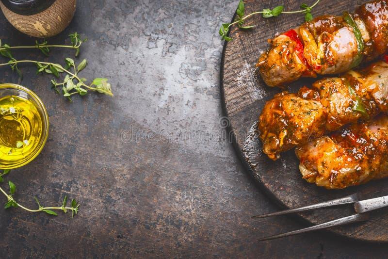 Grilla matbakgrund med den marinerad steknålar, köttgaffeln, örtkryddor och olja på mörk rostmetallbakgrund, bästa sikt royaltyfri bild