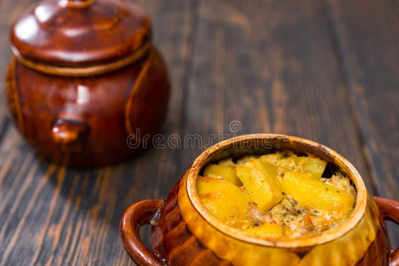 Grilla potatisar, ost och kryddor i en lerakruka på ett träskrivbord arkivfoto