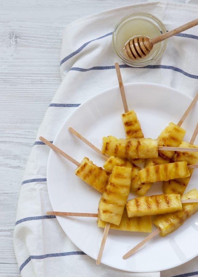 Grillad ananas på bambupinnar med honung på en vit träbakgrund, bästa sikt Fr?n ?ver framl?nges lekmanna-, ?ver huvudet arkivfoto