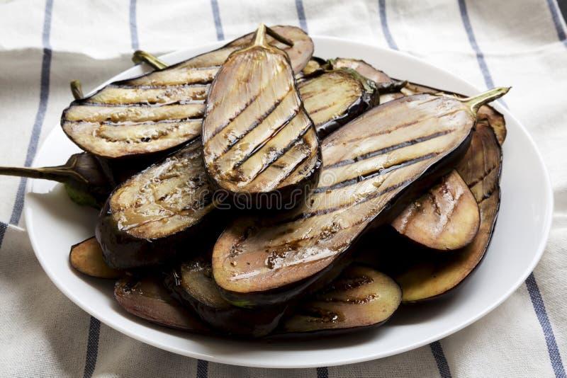 Grillad aubergine på en vit platta, sidosikt closeup royaltyfri bild