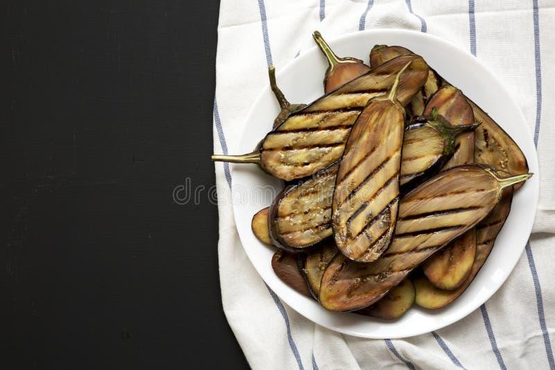 Grillad aubergine på en vit platta på en svart bakgrund kopiera avst?nd fotografering för bildbyråer