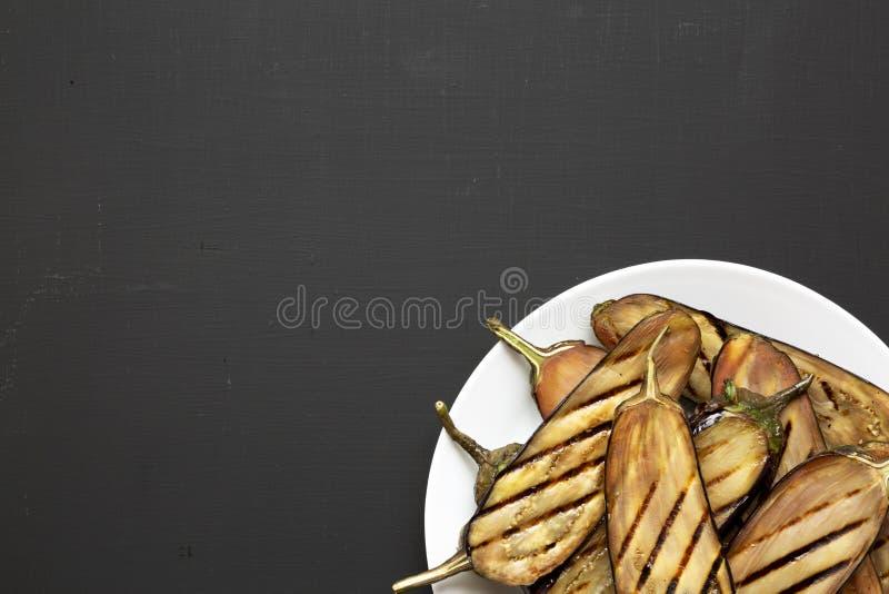 Grillad aubergine på en vit platta på en svart yttersida kopiera avst?nd royaltyfri foto