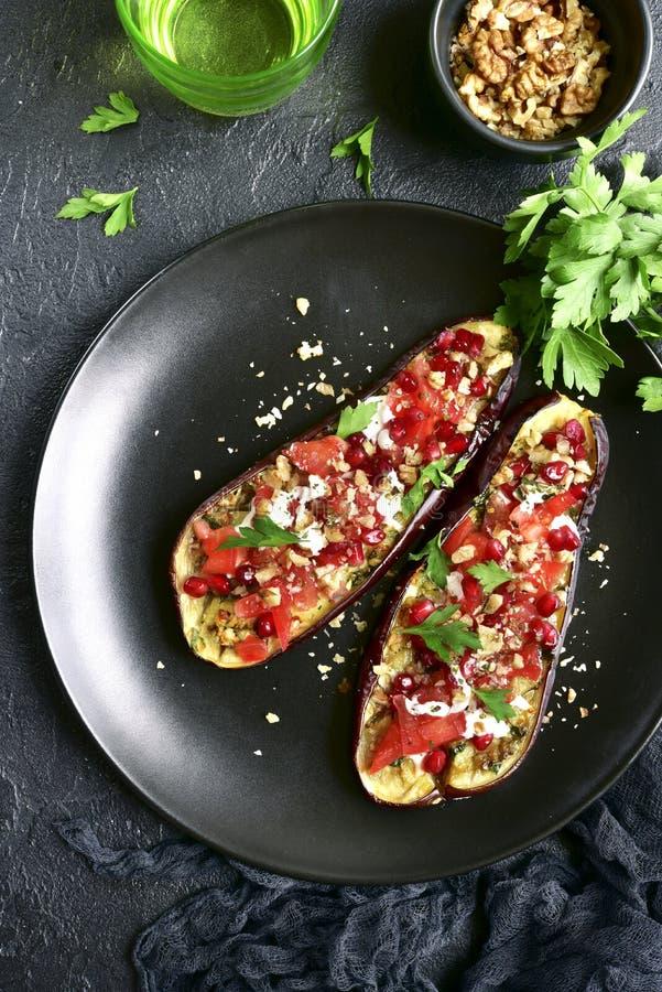 Grillad aubergine som är välfylld med tomater, muttrar, granatäpplet och yo arkivfoto