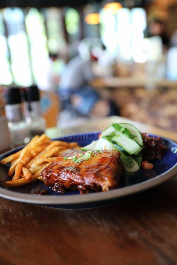 Grillad biff för grisköttstöd med nya grönsaker på ett gammalt lantligt trä i restaurang arkivfoton