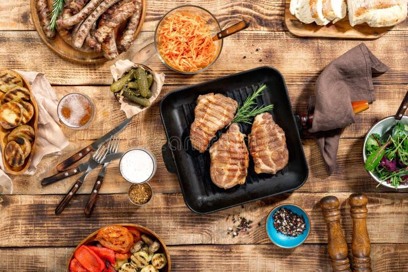 Grillad biff, korvar, öl och grillade grönsaker på trä royaltyfri fotografi