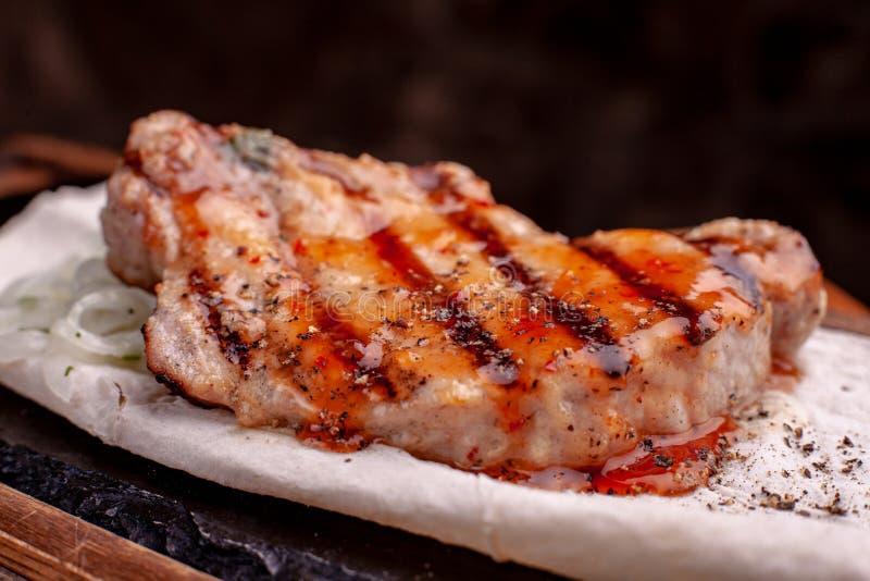 Grillad biff med franska småfiskar och grönsaker tjänade som på den svarta stenen på trätabellen med röd sås royaltyfri fotografi