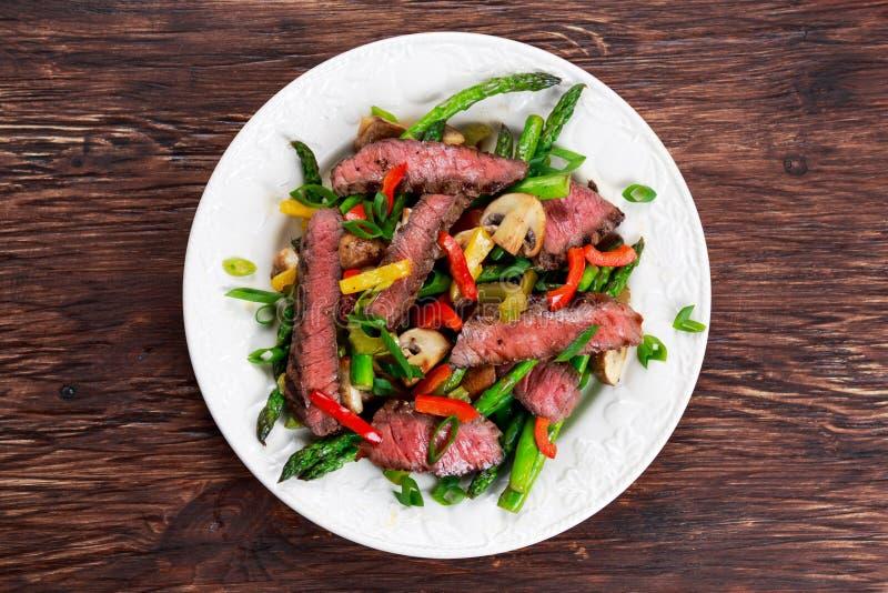 Grillad biff med stekte under omrörning grönsaker på plattan royaltyfri fotografi