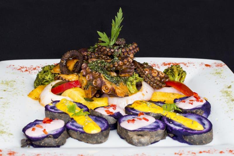 Grillad bläckfisk, gourmet- maträtt från Peru Tjänat som med purpurfärgade potatisar (nativaen) royaltyfri bild