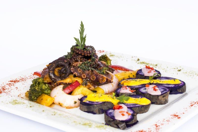 Grillad bläckfisk, gourmet- maträtt från Peru Tjänat som med purpurfärgade potatisar (nativaen) arkivfoto