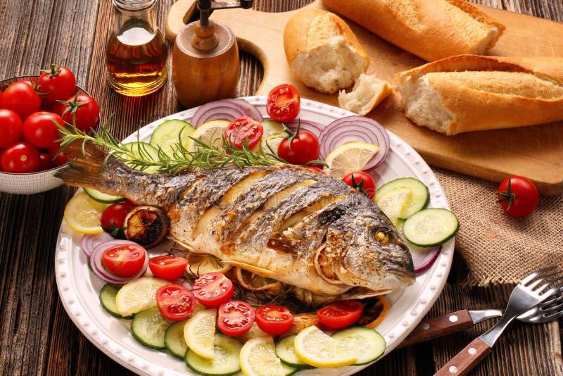 Grillad doradafisk med grönsaker på träbakgrund fotografering för bildbyråer