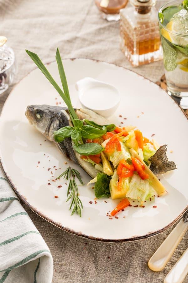 Grillad doradofisk som stoppas med olika grönsaker på den vita plattan som tjänas som på tabellen royaltyfria bilder