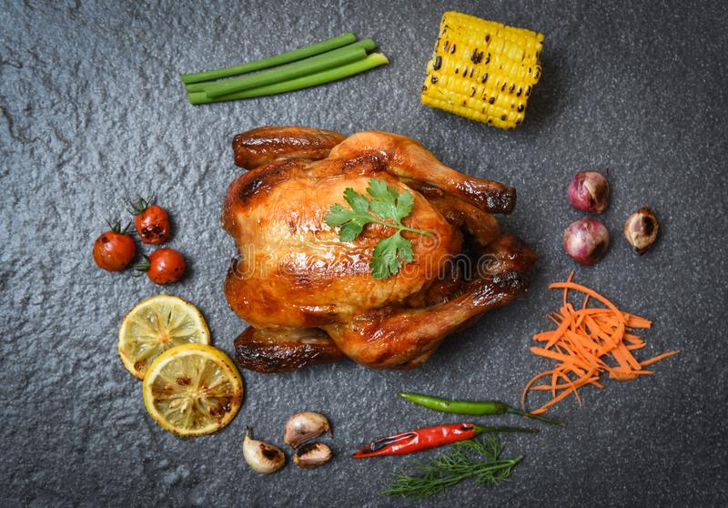 Grillad feg/bakad hel höna som överst grillas med på örter och kryddor och mörk sikt för bakgrund royaltyfri fotografi